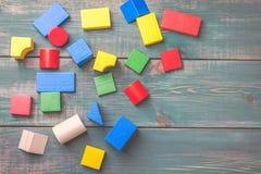 孩子逻辑思维的几何形状 在绿色木背景的五颜六色的木块 儿童` s积木 免版税图库摄影