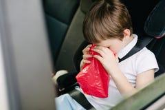 孩子遭受在汽车的晕动病 免版税库存照片