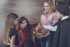孩子采取从妇女给他们的万圣夜党带来的花瓶的甜点 库存图片