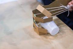 孩子采取有纸板机械臂的塑料杯子 词根 免版税库存图片