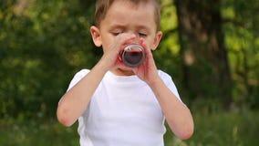孩子采取玻璃玻璃用莓果明亮的红色汁液并且喝它在自然背景  关闭 股票录像