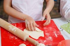 孩子铺开烘烤的面团 免版税库存照片