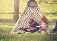 孩子阅读书外面在帐篷圆锥形帐蓬 免版税库存照片