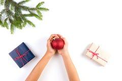 孩子顶视图递拿着圣诞节装饰 礼物盒和圣诞树在白色桌上分支 图库摄影