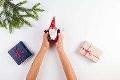 孩子顶视图递拿着圣诞节装饰 礼物盒和圣诞树在白色桌上分支 免版税库存照片