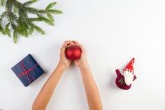 孩子顶视图递拿着圣诞节装饰 礼物盒和圣诞树在白色桌上分支 库存图片