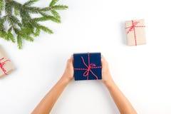 孩子顶视图递拿着礼物 礼物盒在工艺纸和在白色背景的圣诞树分支包装了 库存照片