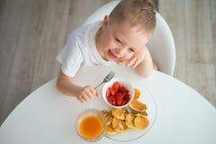 孩子食用早餐在一个晴朗的早晨 免版税库存照片