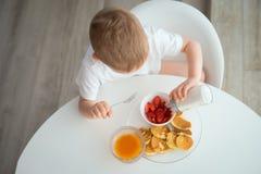 孩子食用早餐在一个晴朗的早晨 图库摄影