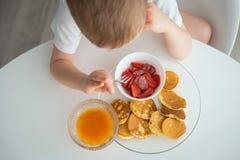 孩子食用早餐在一个晴朗的早晨 免版税图库摄影
