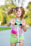 孩子骑马滑行车 免版税图库摄影