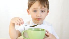 孩子高兴地吃从盘的汤与匙子,特写镜头 免版税图库摄影