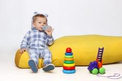 孩子,人们,家庭,生活方式概念 使用与有些玩具和喝从一个sippy杯子的射击一个小男婴 免版税库存照片