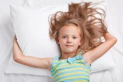 孩子,唤醒和床时间概念 小可爱的轻松的女孩,打扮在偶然成套装备,感到轻松在舒适的床上 库存图片