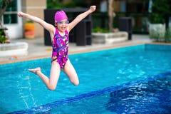 孩子,女孩,跳进充满乐趣和幸福的游泳池 免版税图库摄影