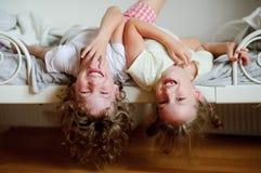 孩子,男孩和女孩,淘气在床上在卧室 免版税库存图片