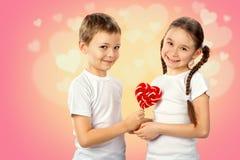 孩子,男孩给一个小女孩糖果在心脏形状的红色棒棒糖在桃红色背景 库存图片