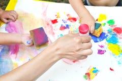 孩子绘一个在纸片的生动的手指油漆 免版税库存图片