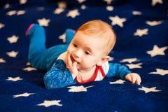 孩子6个月和在家微笑在满天星斗的天空的一条蓝色毯子 库存照片