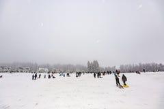 孩子滑冰在冬天跑的雪橇 图库摄影