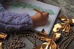 孩子给圣诞老人写信并且画圣诞树 库存照片