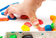 孩子从在桌,有彩色塑泥的手上的彩色塑泥铸造 库存图片