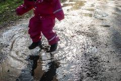 孩子/女孩有桃红色雨衣跳跃的水池/水坑的 库存照片