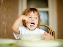 孩子从有匙子的板材吃 免版税库存图片
