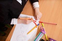 孩子画毡尖的笔 小孩子拿着一支蓝色毡尖的笔手中并且画抽象公主城堡 画的孩子, s 库存图片