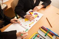 孩子画毡尖的笔 小孩子拿着一支蓝色毡尖的笔手中并且画 画的孩子,一套色的毛毡笔  库存图片