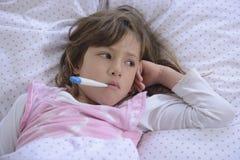 孩子以热病在床上 免版税库存照片
