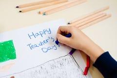孩子画他的学校课程的老师一幅蜡笔画  免版税库存图片