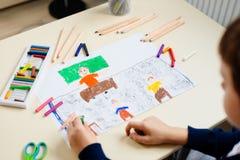 孩子画他的学校课程的老师一幅蜡笔画  库存图片