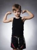 孩子 滑稽的男孩一点 炫耀显示他的手二头肌肌肉的英俊的男孩 库存照片