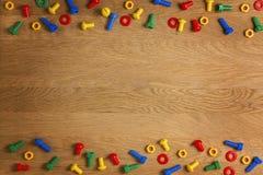 孩子建筑戏弄螺丝和坚果在木背景 顶视图 平的位置 复制文本的空间 免版税图库摄影