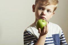 孩子&苹果 小男孩用绿色苹果 背景玉米片食物健康宏观工作室白色 果子 免版税库存照片