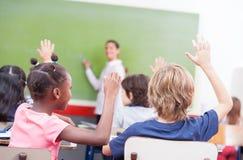 孩子画象举了他们的在一多种族classr的手 库存图片