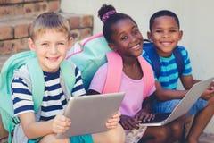 孩子画象使用一种膝上型计算机和数字式片剂的在台阶 免版税图库摄影