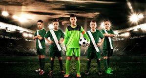 孩子-足球冠军 橄榄球运动服的男孩在有球的体育场 与足球队员的体育概念 免版税库存图片