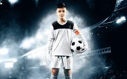 孩子-足球冠军 橄榄球运动服的男孩守门员在有球的体育场 概念查出的体育运动白色 图库摄影