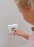 孩子黏附在插口的手指 免版税库存图片