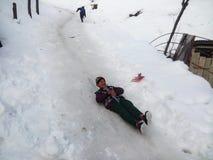 孩子滑雪享受冬天 库存照片