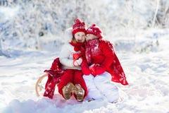 孩子sledding在冬天森林孩子喝在雪的热的可可粉 免版税库存图片