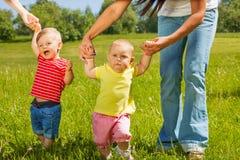 婴孩学会如何走握母亲手 免版税库存照片