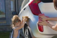 婴孩帮助妈妈洗涤汽车 免版税库存照片