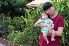 婴孩微笑与举行在庭院里愉快地递母亲 库存图片
