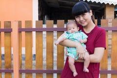 婴孩微笑与举行在房子里愉快地递母亲 库存照片