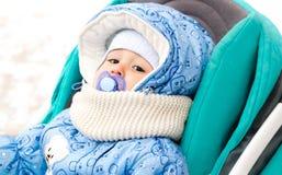 婴孩愉快笑享受步行在坐在有羊皮敞篷的一辆温暖的婴儿推车的一个多雪的冬天公园 图库摄影