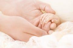 婴孩手,母亲举行婴儿,做父母新出生的孩子帮助 免版税图库摄影