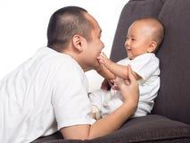 婴孩接触爸爸面孔 免版税库存照片